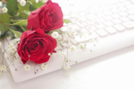 パソコンのキーボード、メモ帳とボールペン、スマホとイヤフォン、電卓、セルロイドフレームの眼鏡。