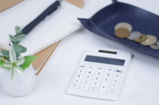 メモ帳とボールペン。電卓とコインの載ったレザートレイ。卓上サイズの観葉植物。