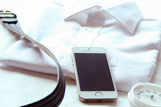 朝の身支度。きちんと畳まれたビジネスシャツ。ベルト。スマートフォン。目覚まし時計。