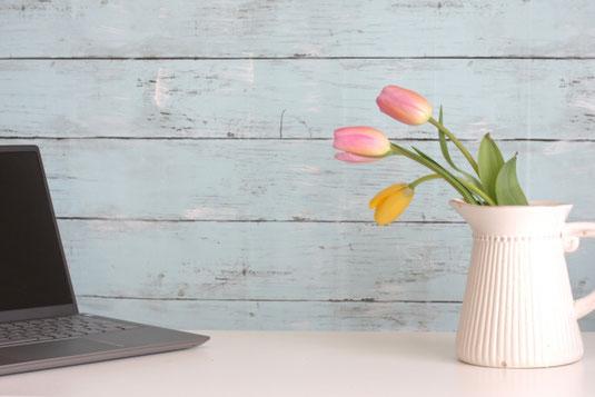 デスクのうえに置かれた腕時計。コーヒーの入ったマグカップ。カスミソウが生けられた花びん。