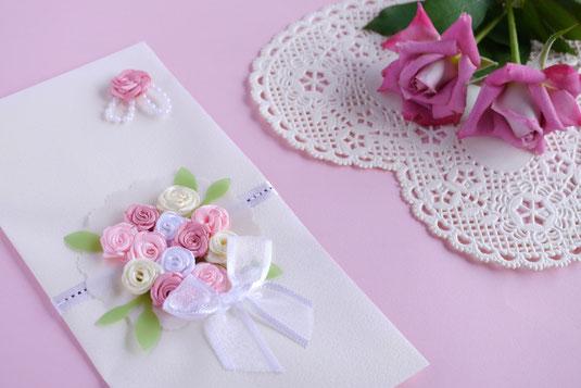 ブーケのコサージュが貼られた記念のサイン帳。レースのテーブルクロスのうえにピンクのバラが2輪。