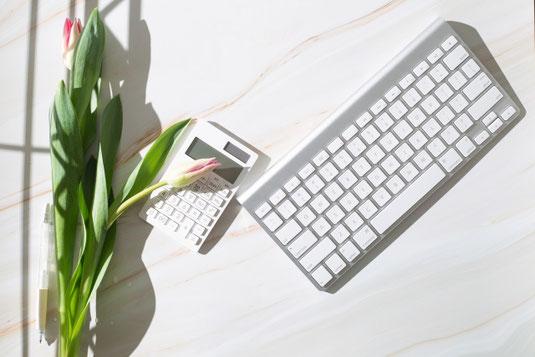 陽ざしが差し込むデスク。白の電卓とパソコンのキーボード。チューリップの花。