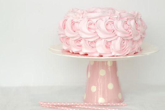 お祝いのケーキ。ピンクのクリームでバラの花がデコレーションされている。