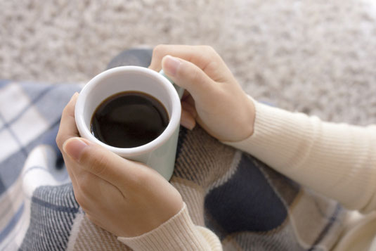 チェック柄のブランケットにくるまり、ホットコーヒーのマグカップを抱える手。