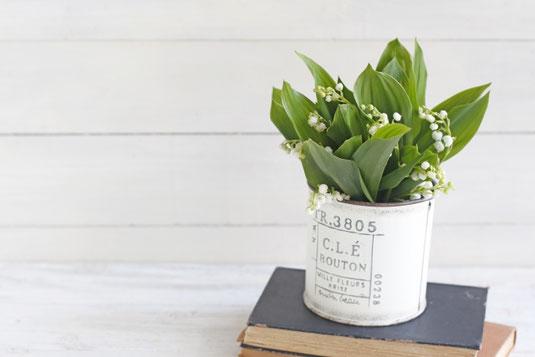 パソコンのキーボード、スマホ、イヤホン、ダブルクリップ。コーヒーの入ったカップ&ソーサとストロベリーチョコ。無造作に置かれたピンクのバラの花。