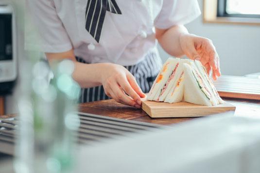 カフェのティーセット。かごのトレイにカヌレとアイスカフェラテ。チューリップの花。置時計とライトシェード。