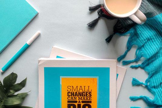 紫と白の花が白い花びんに活けられている。傍らにコーヒーの入ったカップ。ページの開かれた本のうえに眼鏡が置かれている。