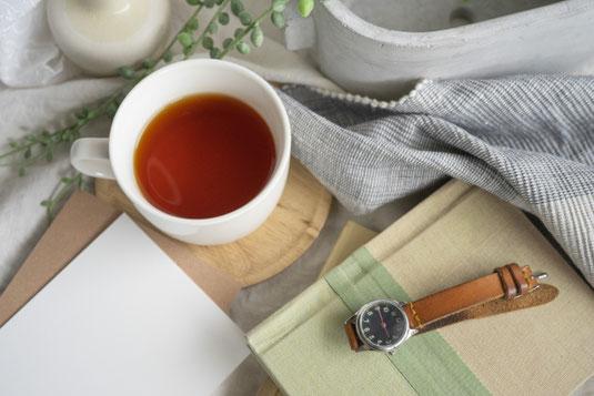 ピンクのバインダーノートと白の電卓。観葉植物のグリーンのつる。