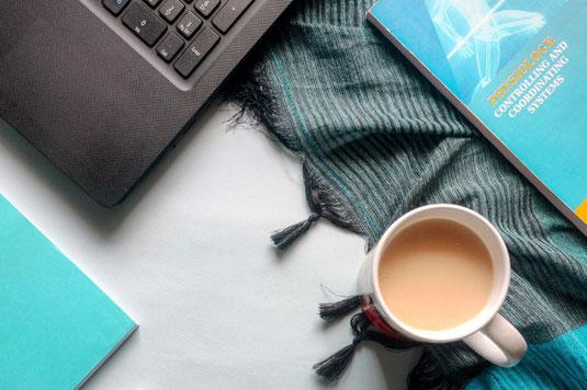 ページが開かれたスケジュール帳とカレンダー。CHECK!と書かれたメモ。カラフルな付箋とボールペン。