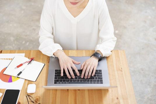 フリーアドレスのオフィス。デスクでノートパソコンと資料、手帳を広げて仕事するビジネスウーマン。
