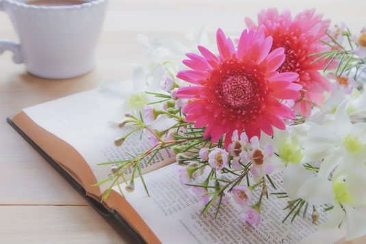 ページの開かれた書籍。ガーベラとマーガレットの花束。コーヒーの入ったカップ。