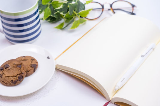 デスクに広げられたノートとボールペン。マグカップとチョコチップクッキーが載ったお皿。リーディンググラス。観葉植物のグリーン。