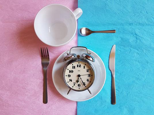 朝食のテーブル。スープカップ、お皿、ナイフとフォーク。お皿の上に目覚まし時計。