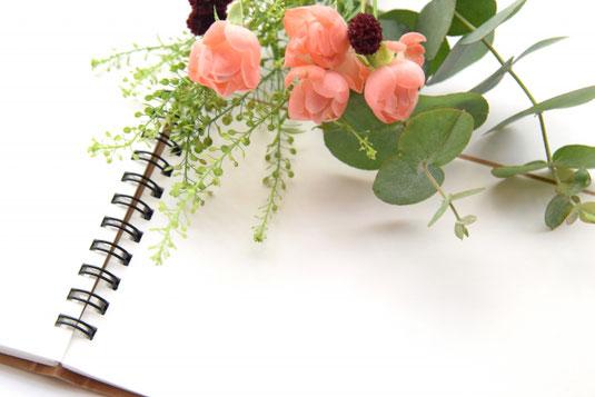 広げられたリングノートのうえに無造作に置かれたピンクのちいさなバラ。