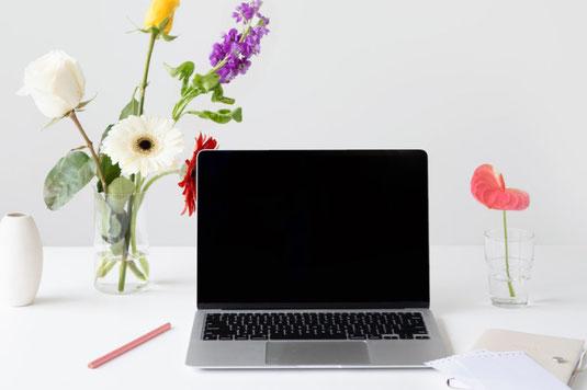 マーブル調のテーブルに置かれたユーカリの小枝と置時計。広げられた手帳とボールペン。黄色とオレンジの付箋。