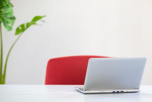 オフィスのテーブルに広げられたノートパソコン。赤のチェア。観葉植物のグリーン。