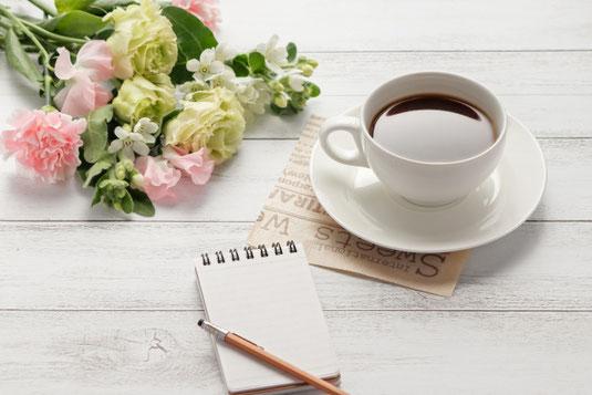 テーブルに無造作に置かれたバラのブーケ。コーヒーの入ったカップ&ソーサ。メモ帳と鉛筆。