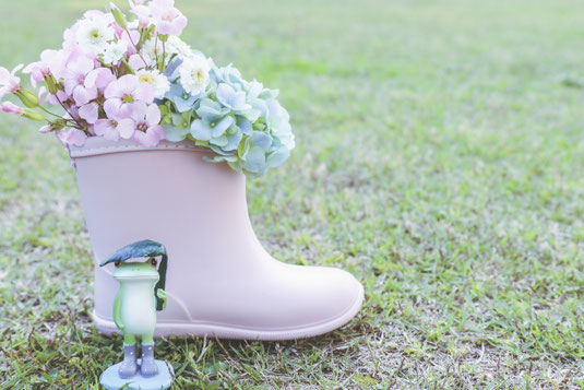 芝生のグリーンのうえに置かれたミニチュアの黒板。チョークで書かれた日本地図と晴れと雨マーク。その横にちょこんとすわったカエルのおもちゃ。