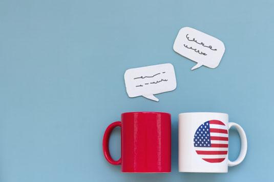 赤のマグカップとアメリカの国旗が印刷された白のマグカップ。横に並んで英会話。