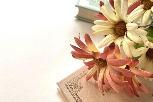 ページが開かれた分厚い洋書。紅茶の入ったカップ&ソーサ。ブルースターのブーケ。