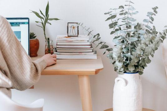 在宅勤務のデスク。ノートパソコン、スマホ、イヤフォン。クッキーの小皿とコーヒーのマグカップ。リーディンググラスと本。