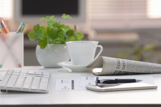 オフィスのデスク。パソコンのキーボードの前に広げられた新聞と資料、スマホ、ボールペン。ペン立てとクローバーの鉢植え。白のカップ&ソーサ。