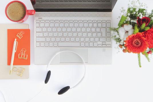 ノートパソコンとヘッドフォン。テレワーク。傍らにガーベラのブーケ。コーヒーの入った赤のマグカップ。メモ帳とボールペン、ダブルクリップ。