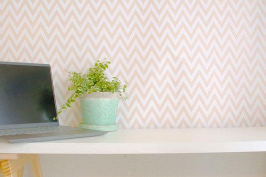 テーブルに置かれたノートパソコン。キーボードパットのうえに置かれた赤のフレームの眼鏡。小さなガラス瓶に活けられたピンクのデイジーとカスミソウ。