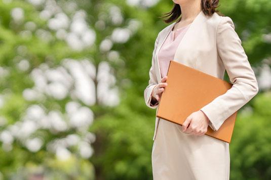 パソコンのキーボード。メモファイル。眼鏡。万年筆。メモ帳。ゼムクリップ。コーヒーの入ったマグカップ。観葉植物のグリーン。