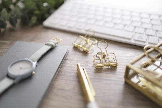 白とゴールドの文房具。パソコンのキーボード、トレイに入ったボールペン。白紙のノートとボールペン。ダブルクリップ、腕時計、ガラスの器に入ったゼムクリップ、ストライプと水玉のマスキングテープ。