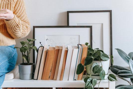 パソコンのキーボードとヘッドフォン。バインダーファイル。無造作に置かれたピンクの小花。