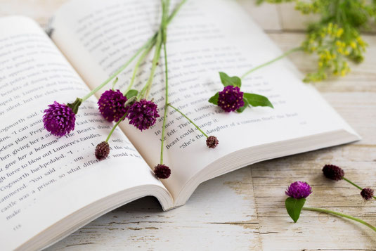 オフィスのデスクに積まれた書籍。黄色の水仙が活けられたガラスの花びん。