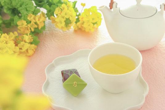 白磁の急須と緑茶の入った湯飲み。抹茶のチョコを添えて。テーブルを囲む菜の花。