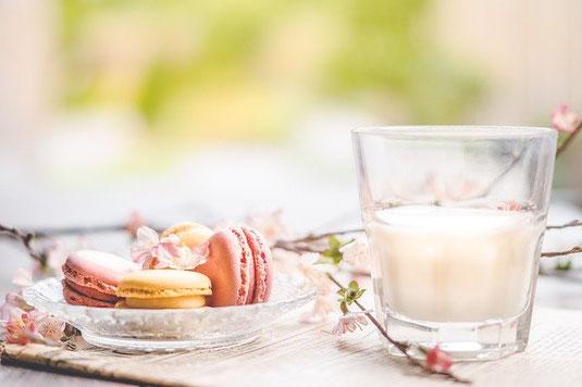 休日の朝のテーブル。カラフルなマカロンが盛られたガラスの皿、ミルクの入ったグラスが置かれたトレイ。桜の枝。
