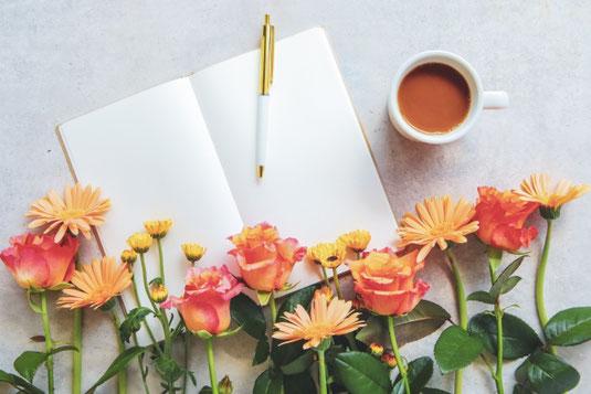 白紙ページの広げられたノートとボールペン。コーヒーの入った白のマグカップ。オレンジピンクのデイジーとバラの花。