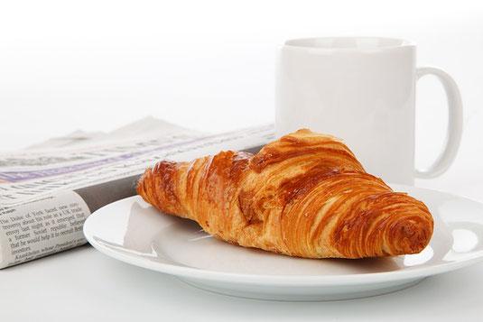 コーヒーの入ったマグカップを片手にノートパソコンのキーボードを操作中。