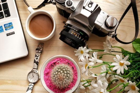 窓辺に飾られたピンクの春の花たち。ガラス瓶に活けられたバラ。ピンクのリボンがかけられたスイトピーの花束。カーネーションのアレンジメント。