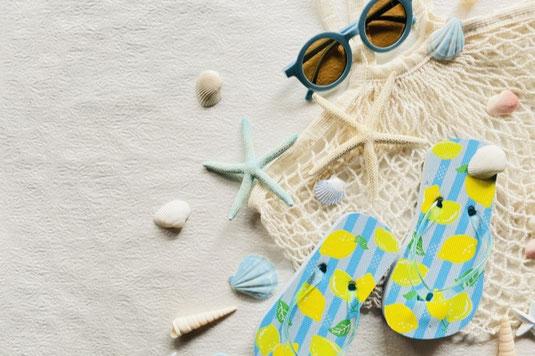 デスクに置かれた花柄の表紙のスケジュール帳。鉢植えの観葉植物。黒インクのびん。シャープペンシル。