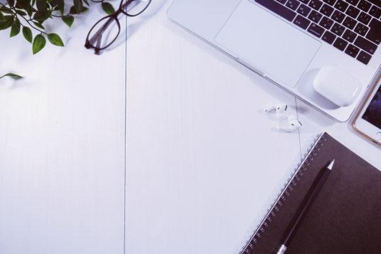 ノートパソコンの前に広げられたメモ帳とボールペン。リーディンググラス。コーヒーの入ったマグカップ。観葉植物のつる。