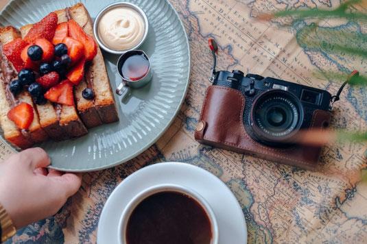 世界地図に目的地を赤いピンでとめる指先。スマホ、ノート、えんぴつ。