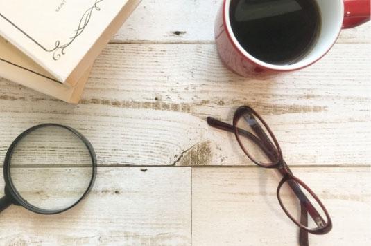 白紙のメモ帳とボールペン。テーブルに無造作に置かれたピンクの小花。