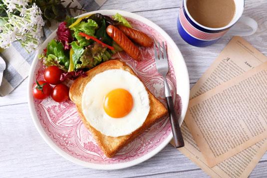 朝の食卓。籐のトレイに盛られたクルミパン。ジャムとママレードの瓶。ティーポットとお皿。