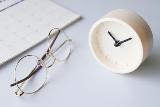 卓上カレンダーの前に置かれた眼鏡と置時計。