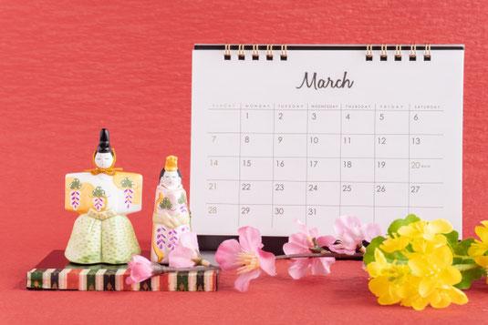 英字新聞のうえに置かれた2月のカレンダーとピンクのバラ。