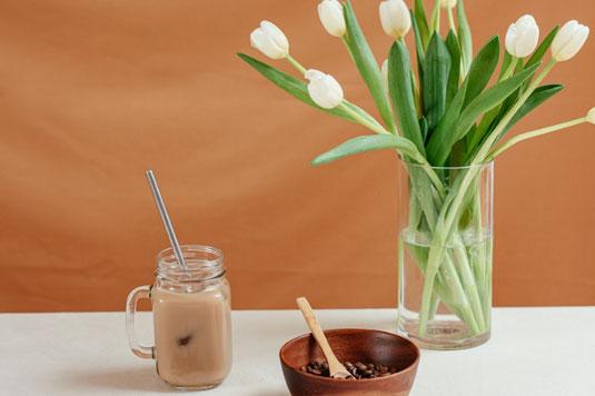 白の置時計とコーヒーの入った白のマグカップ。観葉植物のリーフ。
