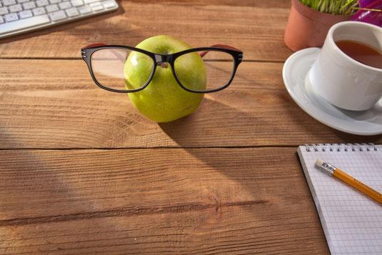 眼鏡がかけられた青りんご。パソコンのキーボード。観葉植物の鉢植え。紅茶の入ったカップ&ソーサ。メモ帳とえんぴつ。