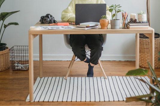 在宅でお仕事中の女性のデスク。ノートパソコン、広げられたノート、メモパッド、メモ帳。ラッピングペーパーと毛糸の玉。バラのブーケ。ペンとコーヒーの入ったマグカップ。