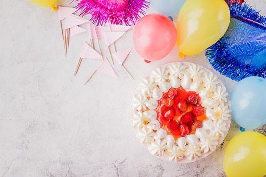 窓辺のテーブル。ページが開かれたハードカバーの本。紅茶の入ったカップ&ソーサ。クッキーのお皿。花びんに活けられた大輪の白のダリア。