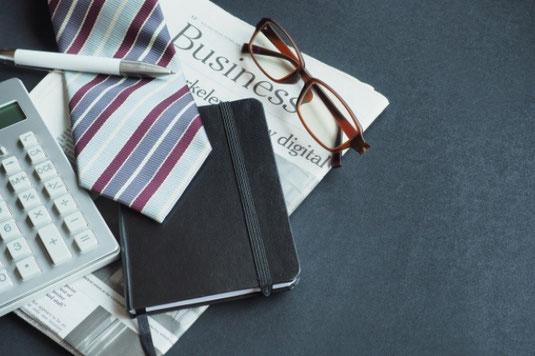 パソコンのキーボード、スマホ、マウス、イヤフォン、電卓、メモ帳、写真フレーム、ボールペンが整然と並んでいる。