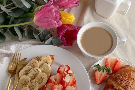 トレイに置かれた紅茶の入ったマグとマカロン。カーネーションとレンギョウのブーケ。休みのひととき。